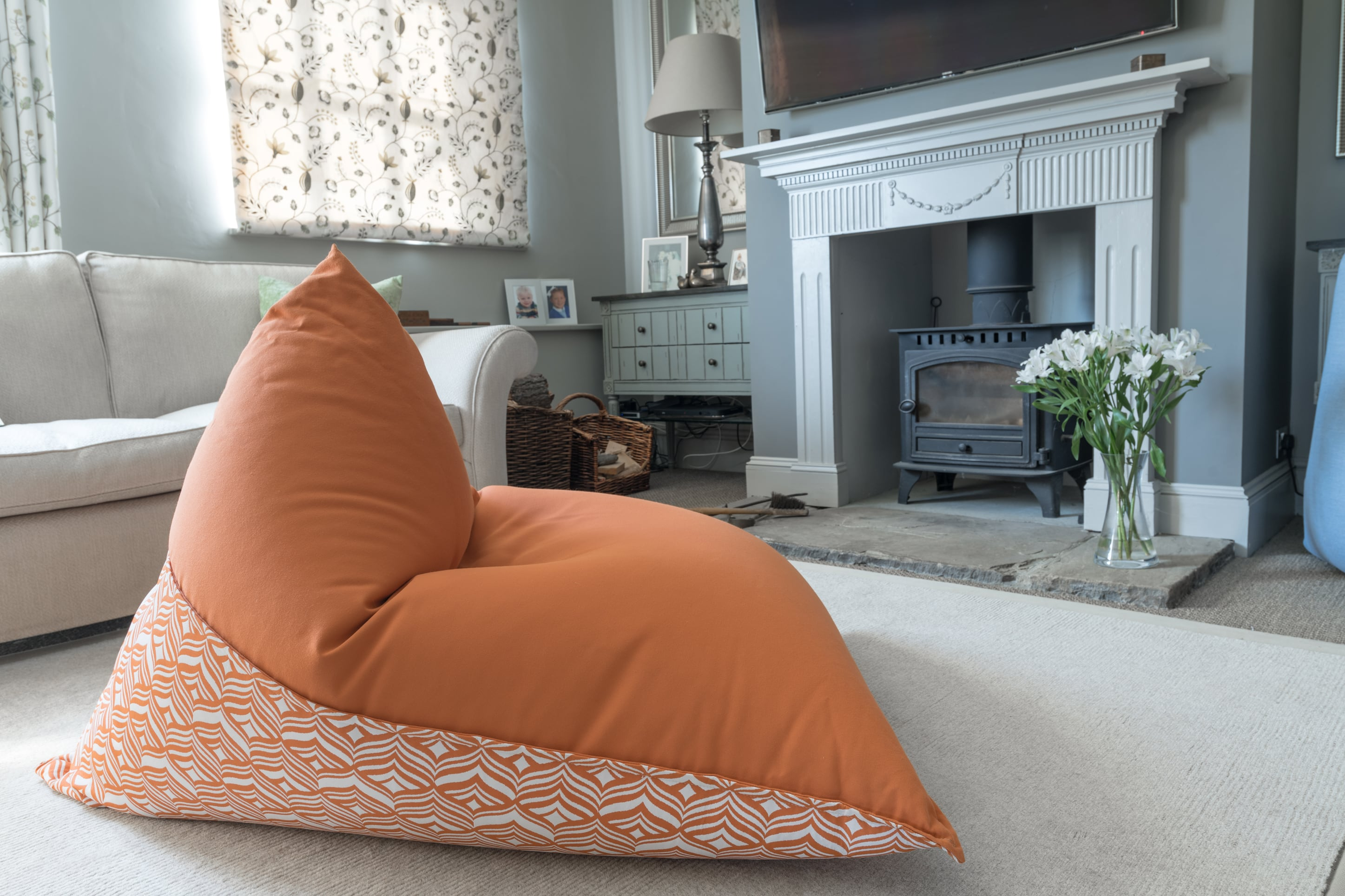 Armadillo Sun bean bag chair in orange and white tulip pattern indoors by fireplace