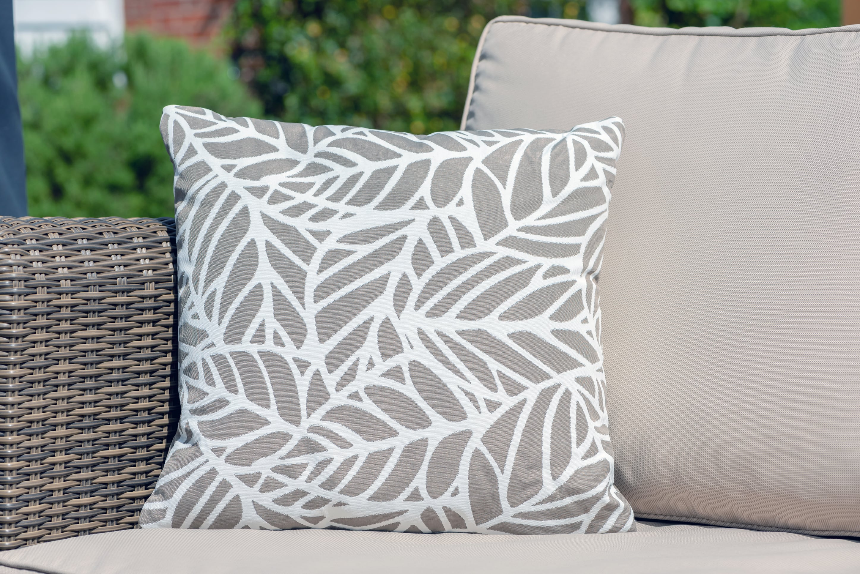 Armadillo Sun waterproof cushion in neutral pumice and white palm pattern