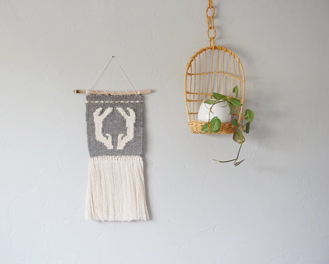 Grey handwoven wall hanging with antlers