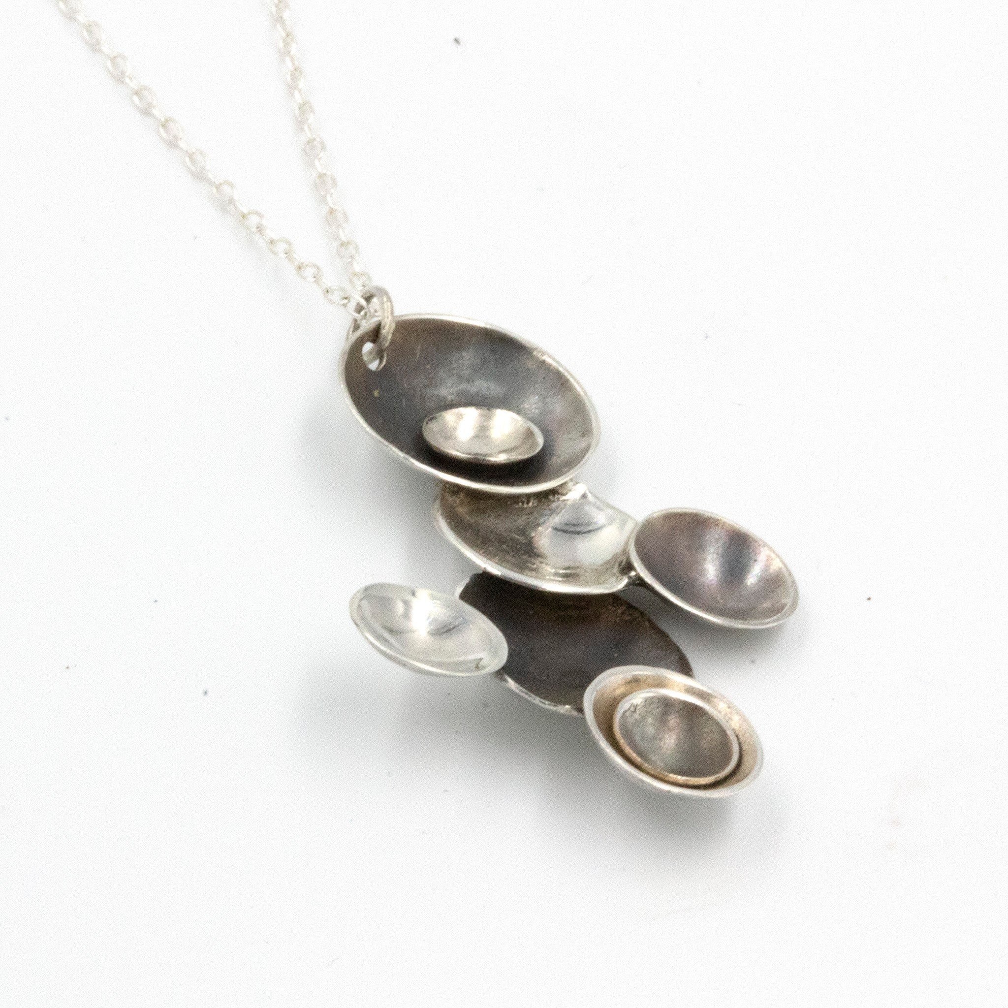 Handmade sterling silver 'Moons' necklace, by Gemma Tremayne Jewellery. This handcrafted necklace is inspired by the alignment of planets and moons in orbit, and features a number of domed  discs, each with a deep patina or high polish. This is a truly elegant and unique piece.