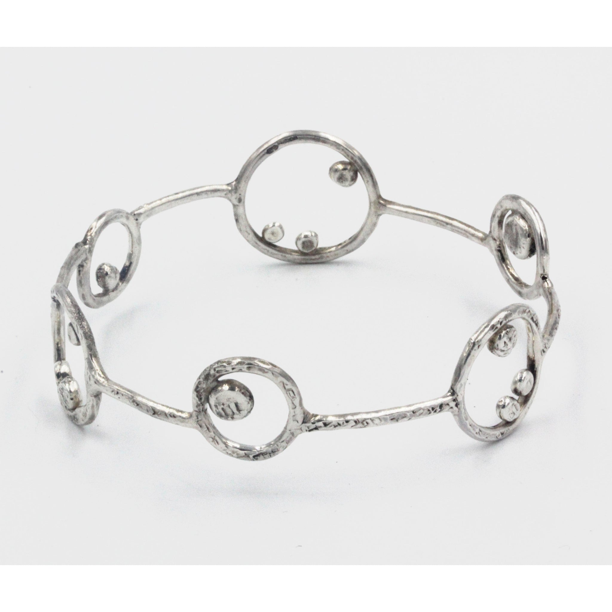 Handmade 'Orbit' Bracelet by Gemma Tremayne Jewellery. Handcrafted in sterling silver, this bangle is inspired by the orbit of planets and moons within our solar system, and features a truly unique design based around circles