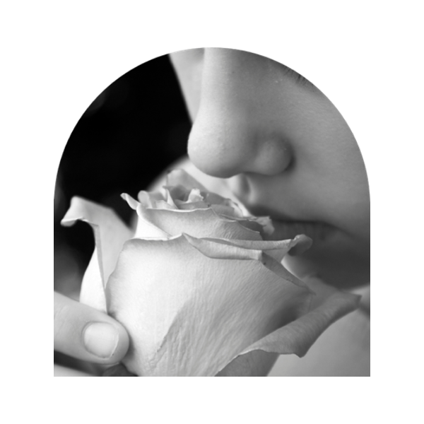 Black & white close-up photo of young girl smelling a flower | Appellation aromas