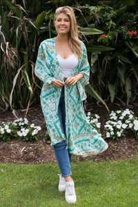 Boho Kimono made from ethically sourced rayon. Colours used in print are mint, pale blue, white and fawn. Print on this kimono is moroccon like with flowers throughout. Length sits just below knees on average size model
