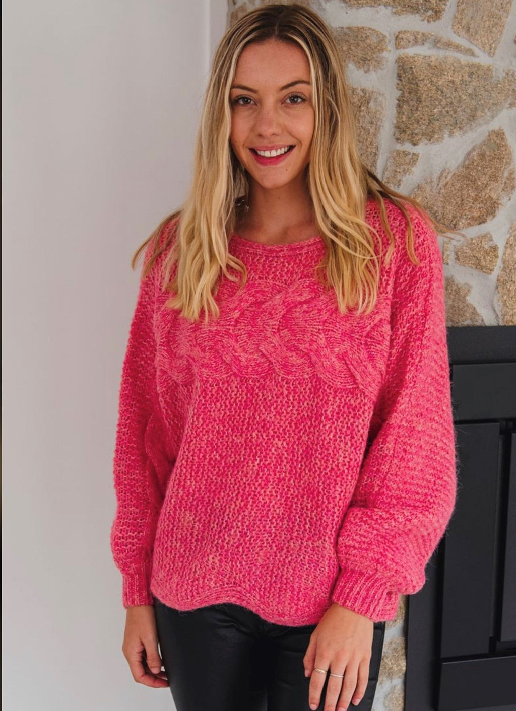 Pink chunky-ish womens knitted jumper. Large scalloped edge on the bottom. Sits just above your bottom at the front and back. Slight yellow marle throughout the pink, not noticeable until you look very closely. Different stitching used to created a wave effect across the breast area continuing down the front of the sleeves. Slight balloon sleeve to the wrist where a cuff is stitched. Scoop neck, not high. 65% Acrylic 35% Wool.