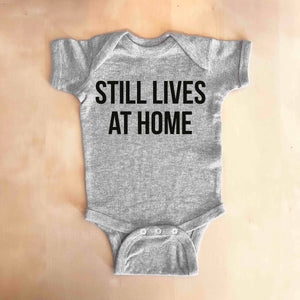 STILL LIVES AT HOME Baby Onesie