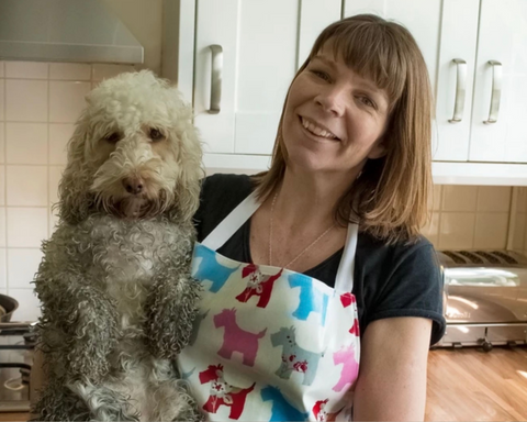 Woman wearing a wipe clean apron with her muddy cockerpoo