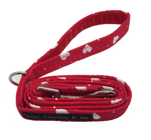 Fabric dog lead designed to co-ordinate with our range of 'My Valentine' dog collars bandanas and bows. Red with white printed hearts dotted all over it    The lead has internal webbing, a heavy duty zinc alloy trigger hook and soft red velvet ribbon lined handle with a D ring for you to clip a treat bag to.   Approximately 105cm long including the trigger hook.