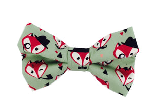 Handmade dog bow tie in cotton print. Made by hand in the U.K. and washable. Sage green with foxy faces printed on.
