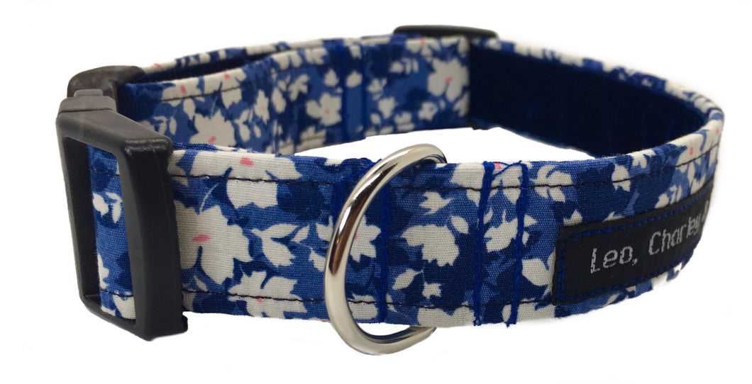 Washable fabric dog collar in a pretty white and orange floral design on a denim blue background.