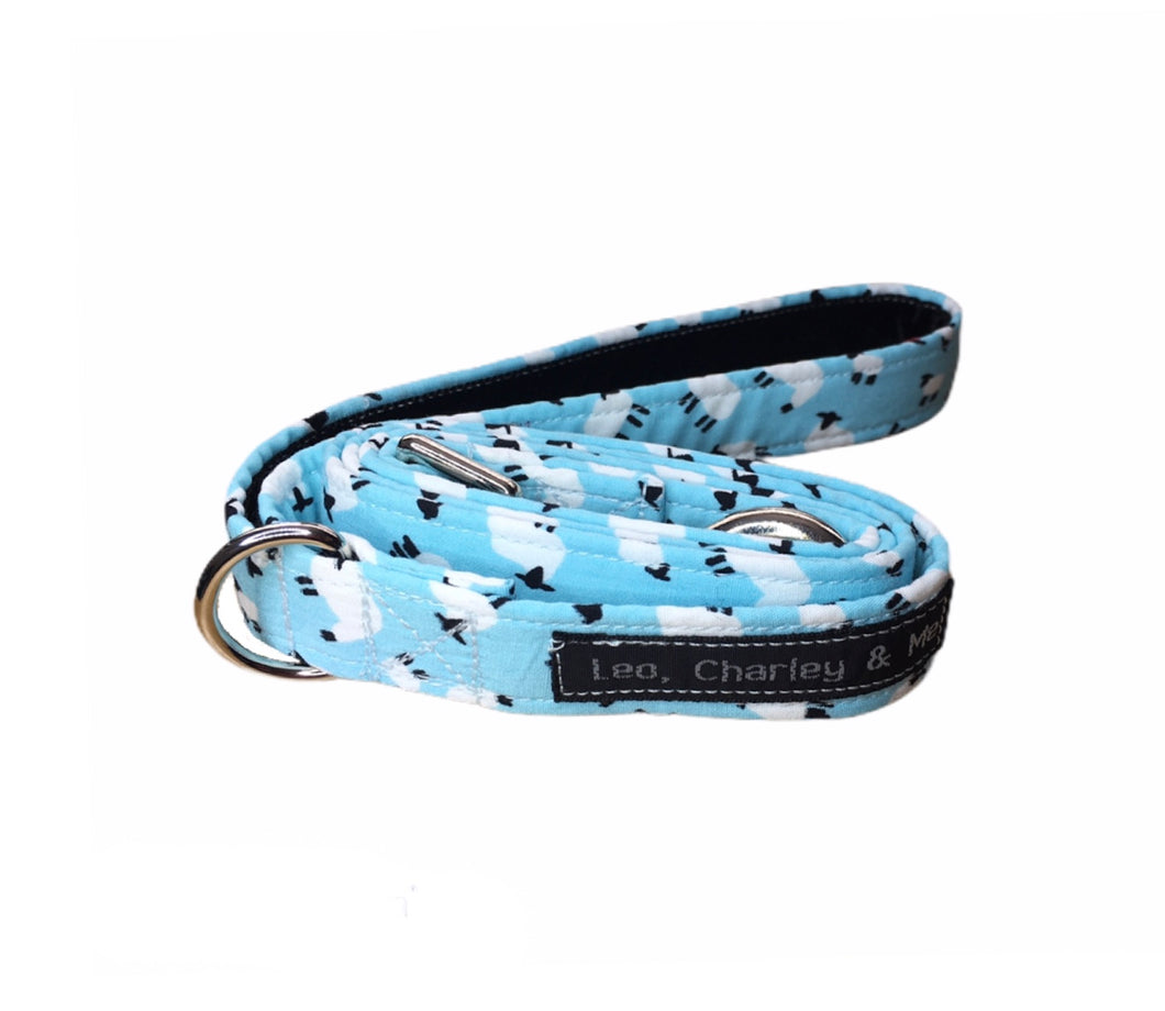 Fabric dog lead in pale blue cotton printed with tiny sheep. Handmade in the U.K. and washable