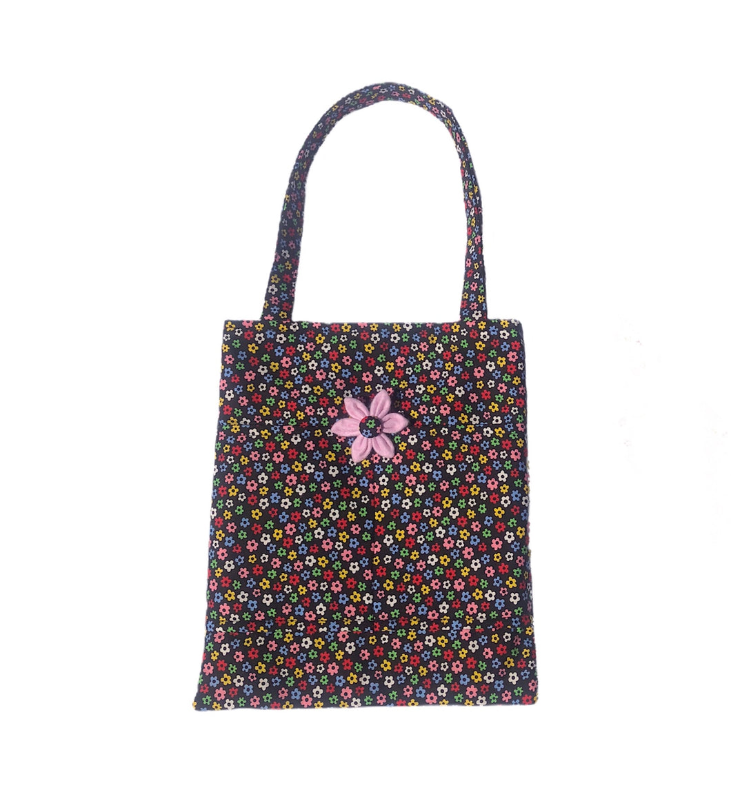 Padded cotton fabric tote bag with internal and external pockets. Ditsy floral print on a black background. Handmade and washable. Made in the U.K.
