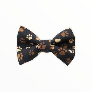 Handmade dog bow tie in cotton print. Made by hand in the U.K. and washable. Black cotton poplin covered in muddy brown paw prints.