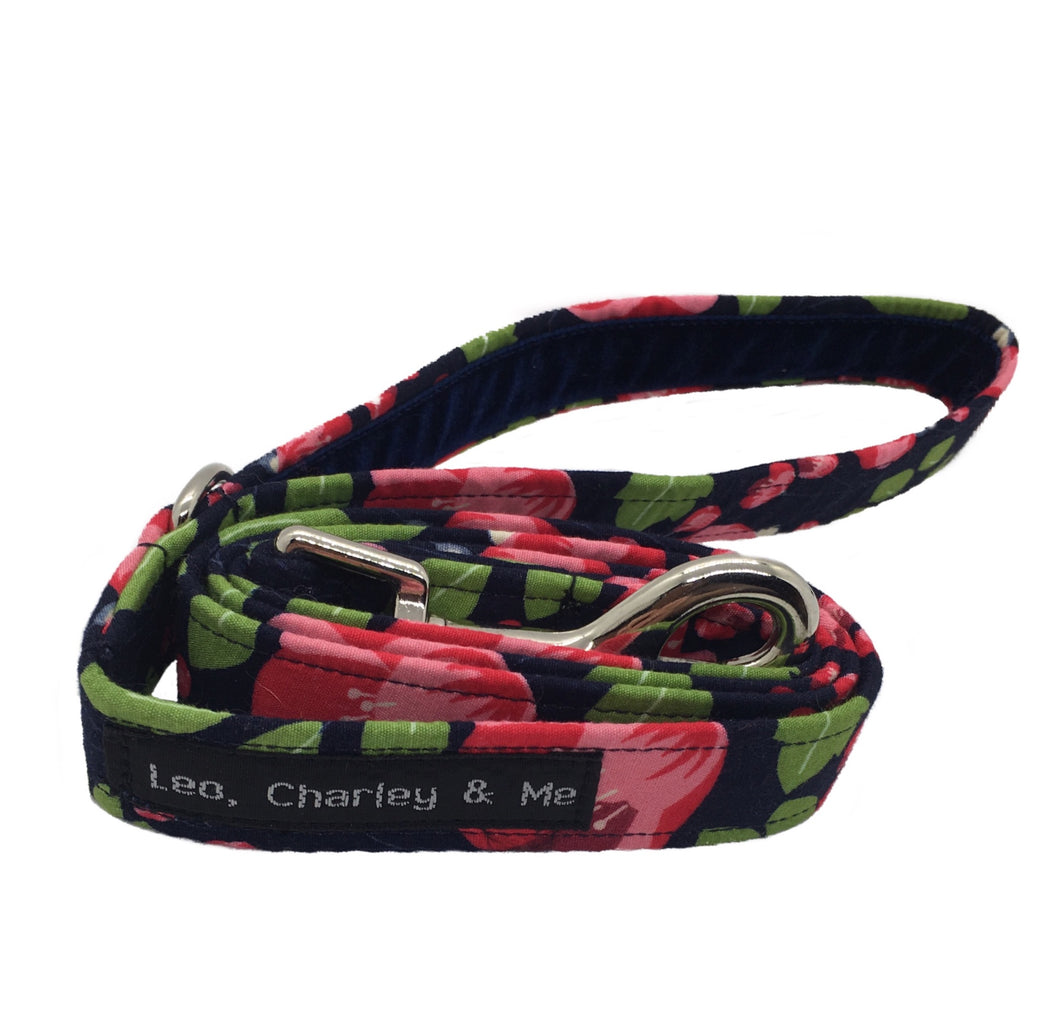 Soft cotton poplin dog lead with pink fuchsias and green foliage on a navy background. It has a soft navy velvet ribbon lined handle. Hand made in the U.K. and washable.