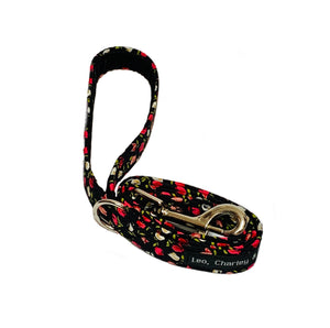 Black fabric dog lead with pretty pink floral print. He's metal alloy trigger hook and a D ring with a velvet ribbon lined handle.  Handmade in the U.K. and washable.