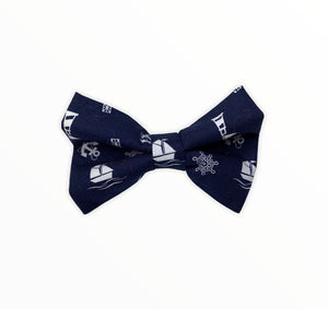 Handmade dog bow tie in cotton print. Made by hand in the U.K. and washable. Navy cotton poplin with nautical symbols and boats.