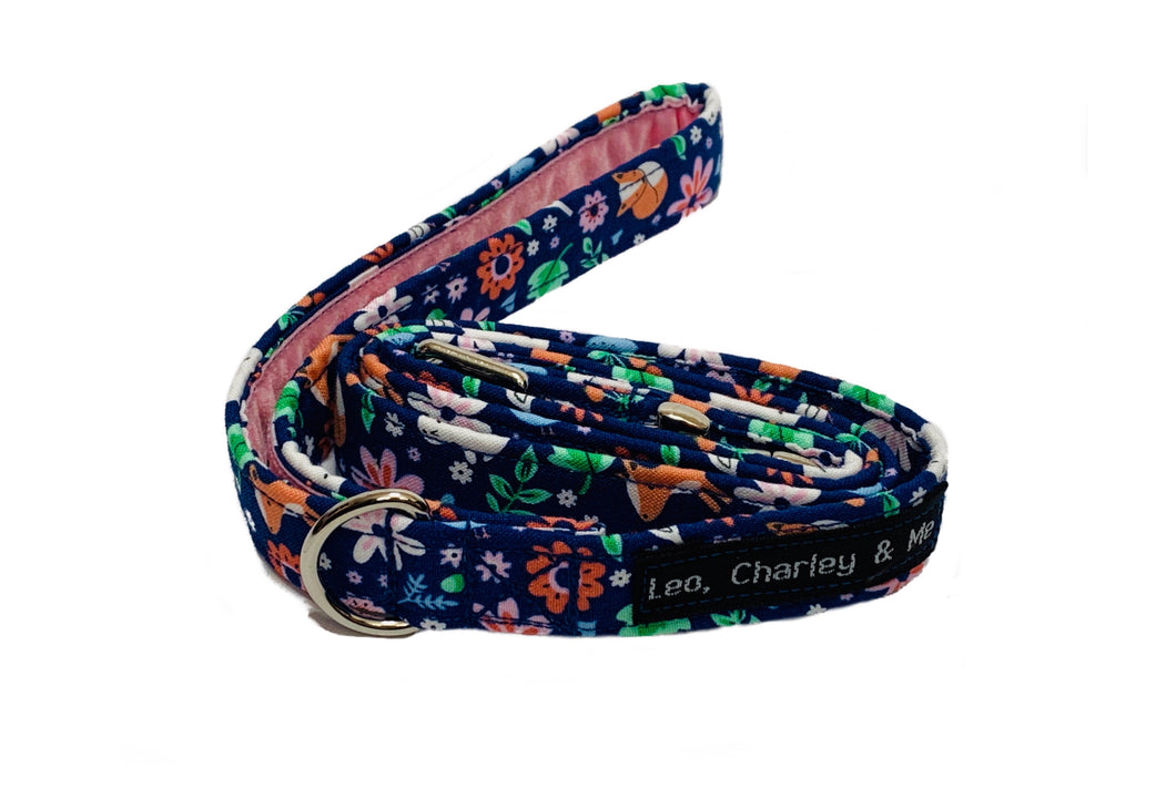 Cotton poplin dog lead in blue with floral and woodland creature print. It has a soft pink velvet lined handle and metal alloy trigger hook with a useful D ring to clip things to. Hand made in the U.K. and washable.