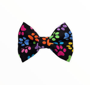 Handmade dog bow tie in cotton print. Made by hand in the U.K. and washable. Black poplin cotton printed with rainbow paw prints.