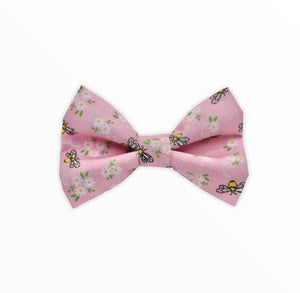 Handmade dog bow tie in cotton print. Made by hand in the U.K. and washable. Pale pink with tiny bees and flowers printed on it.