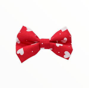 Handmade dog bow tie in cotton print. Made by hand in the U.K. and washable. Valentines bow in red with tiny white hearts.