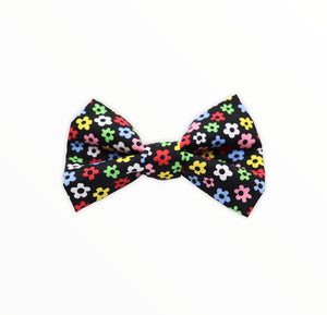 Handmade dog bow tie in cotton print. Made by hand in the U.K. and washable. Black background with multicoloured ditsy daisies.