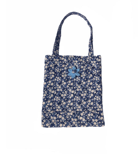 Padded cotton tote in tones of denim blue in a pretty floral print. Handmade and washable made in the U.K.  internal and external pockets with shoulder straps.