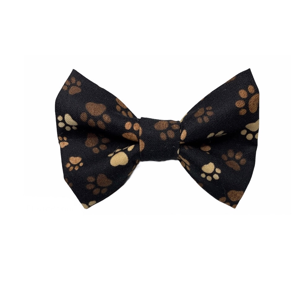 Handmade dog bow tie in cute cotton poplin muddy paw print. Washable and made in the UK. Matching items available