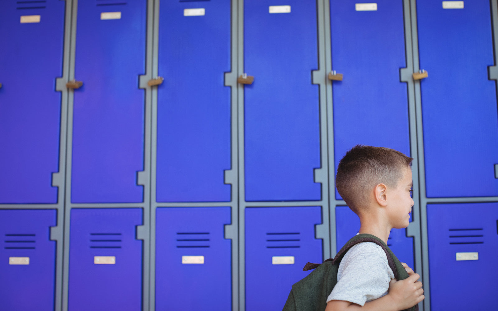 Young boy standing in front of blue plastic clothes lockers