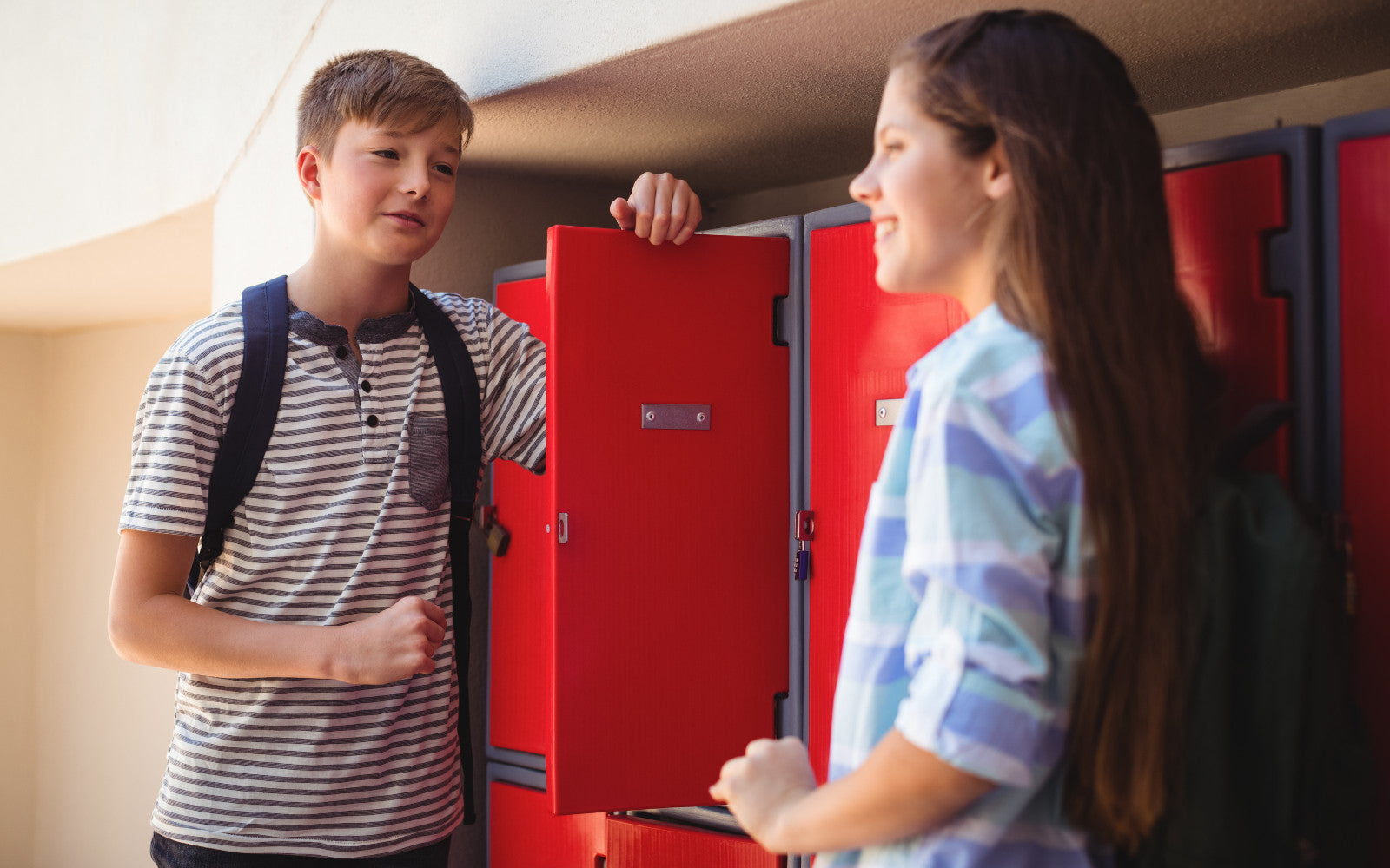 Boy holding red locker door open whilst talking to a girl