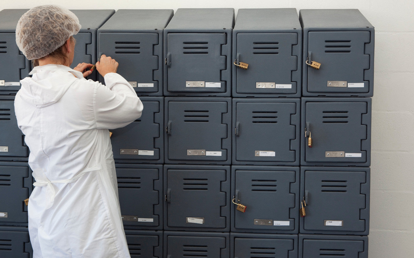 Factory worker in front of grey plastic food lockers