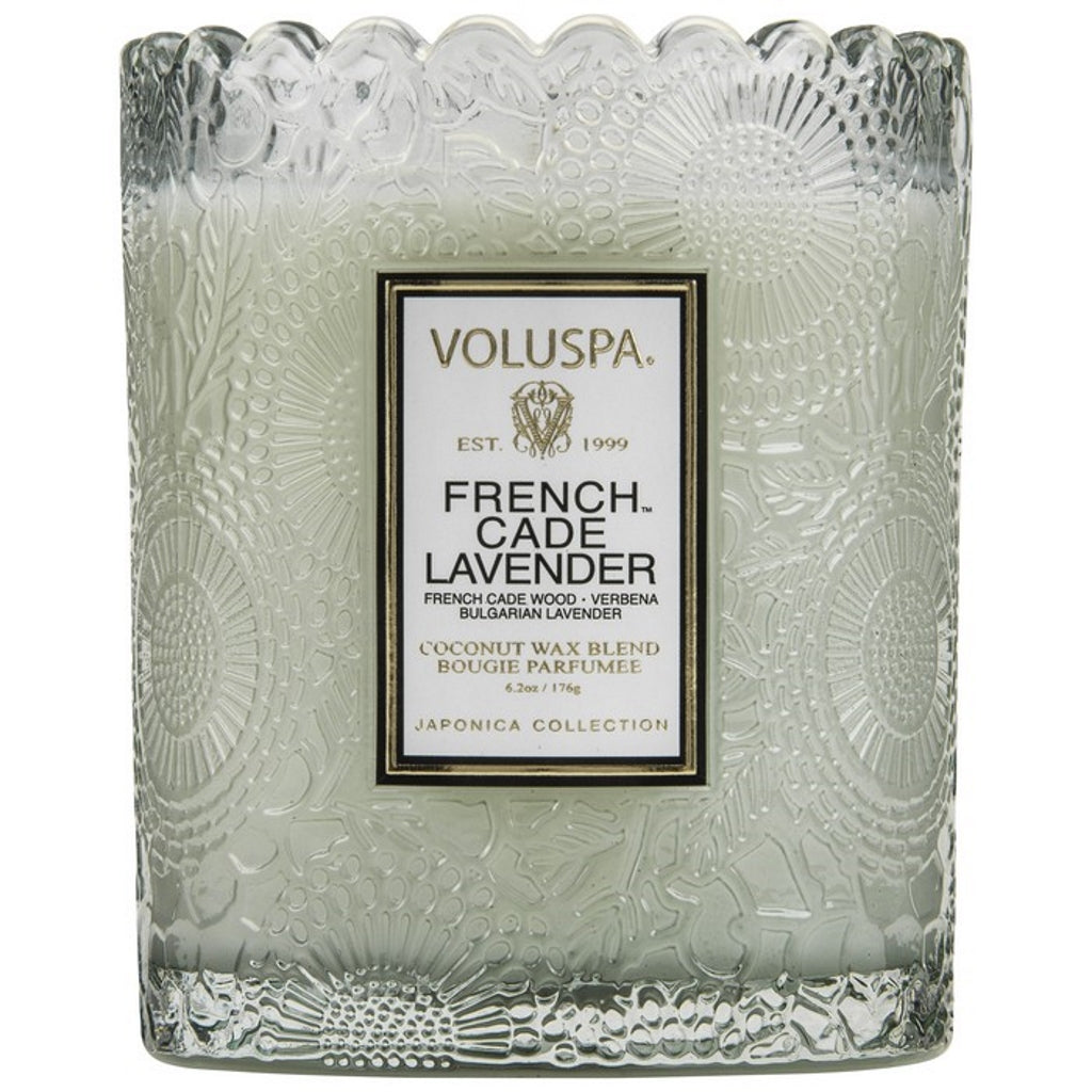 A coconut wax candle in a glass with scalloped edging french cade lavender fragrance