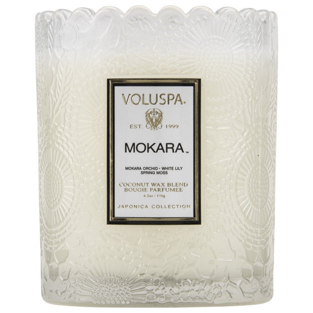 A coconut wax candle in a glass with scalloped edging mokara fragrance