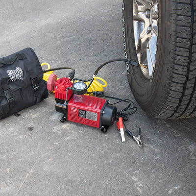 MasterFlow MF-1050 inflator on pavement in use inflating a truck tire.  With carry bag and battery clips