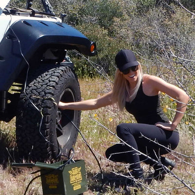 model inflating jeep tire in rugged out door setting with m24o air armor