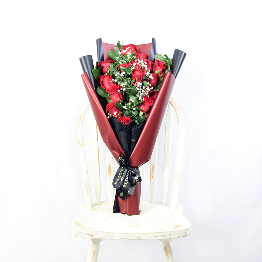 This bouquet includes a selection of deep red roses, baby's breath, and ruscus gathered in floral wrap with designer ribbon.