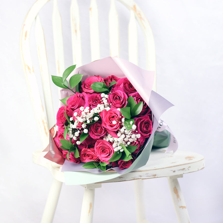 bouquet with pink roses, ruscus and baby's breath wrapped in floral wrap and designer ribbon