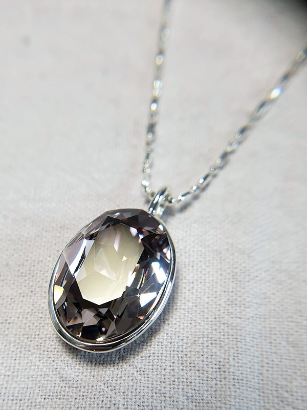 The W Brothers Premium Grade A 925 Sterling Silver Dark Lavender Swarovski Pendant. Our pendant features a brilliant Oval cut synthetic crystal shimmering with Lavender likeliness set on the highest quality silver, perfect for a fashionable statement for men and women's jewelry accessory. Available at www.thewbros.com