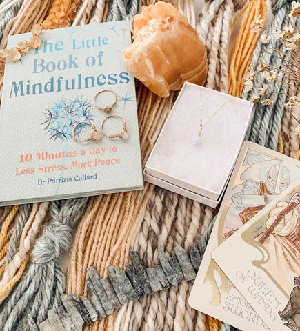 "Blue lace agate drop necklace, various Kindness Gems rings, and ""The Little Book of Mindfulness"""