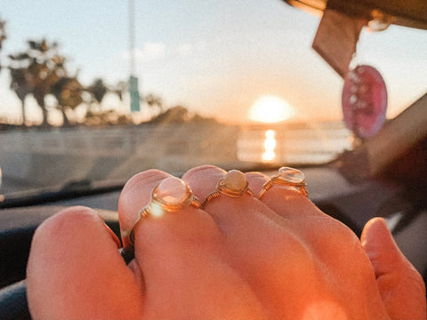 Hand wearing Kindness Gems rings on the dashboard of a car with sunset