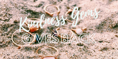 """Kindness Gems Gives Back"" text over Kindness Gems rings on the sand"