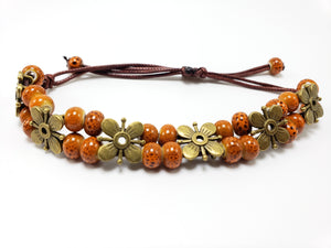 Your purchase of this handmade bracelet with its orange beads and brass flowers helps us rescue girls from sex trafficking!