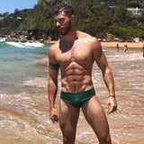 CIRCA75 Men's Chlorine Resistant Swimming Brief Bottle Green on model at beach