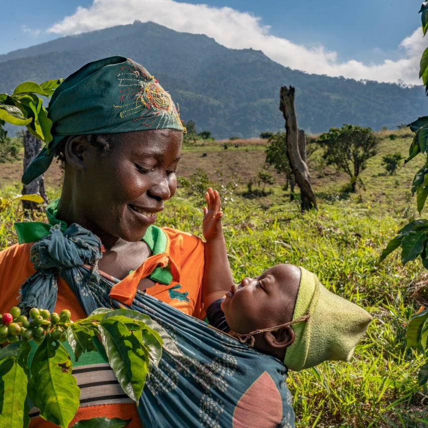 Woman holding baby amid coffee bean plants at Gorongosa National Park.