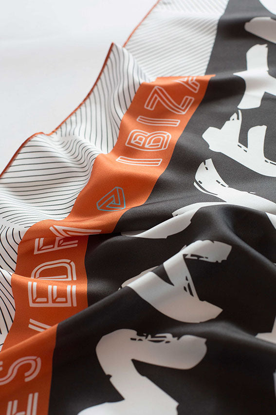 Close up detail of Ibiza silk scarf featuring graphic design of Es Vedra, Ibiza.
