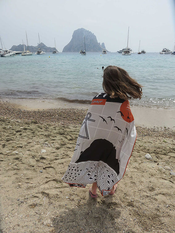 Ibiza silk scarf featuring graphic design of Es Vedra, Ibiza pictured wrapped around young girl at Cala d'Hort beach