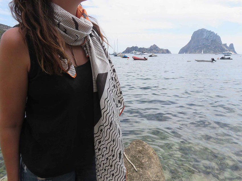 Ibiza silk scarf featuring graphic design of Es Vedra, Ibiza modelled in front of the iconic rocks
