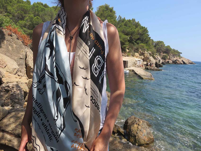 Girl wearing Ibiza silk scarf featuring graphic design of Podenco Ibizan Hound modelled on beach in Ibiza