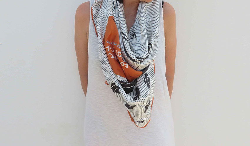 Ibiza silk scarf featuring graphic design of Es Vedra, Ibiza modelled in front of the white wall