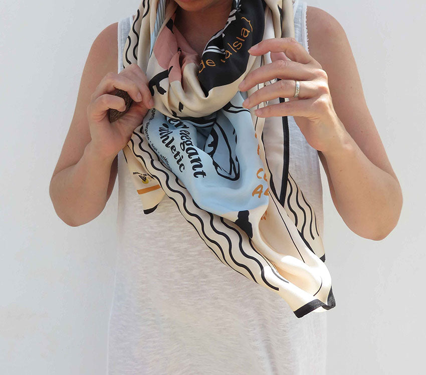 Girl wearing Ibiza silk scarf featuring graphic design of Podenco Ibizan Hound modelled in Ibiza