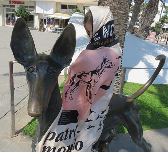 Ibiza silk scarf featuring graphic design of a Podenco / The Ibizan Hound wrapped around young girl on Podenco statue