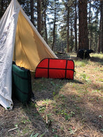 canvas tent with bow cases and bear archery target